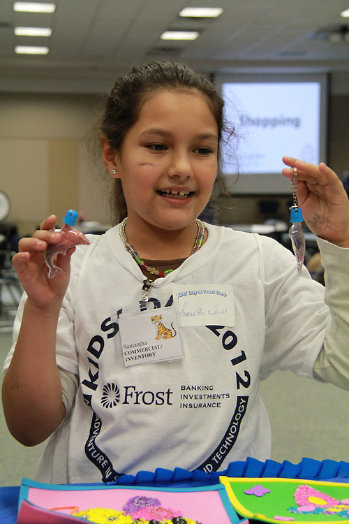 """Samantha Tovar from Park Place Elementary and other students from 14 area elementary and middle schools put their entrepreneurship and banking skills into practice on Dec. 7, at Frost Bank's Kids' Day marketplace. The children, who participate in the Harris County Department of Education's (HCDE) Cooperative for After-School Enrichment programs, hawked backpack ornaments, wacky hair bows, dog tags, pillows, and bowling booths to customers through live """"commercials"""" that they performed and choreographed themselves. They also opened bank accounts and made profit-and-loss projections while selling their homemade wares.<br /> To submit photos for inclusion in eNews, send them to hisdphotos@yahoo.com."""