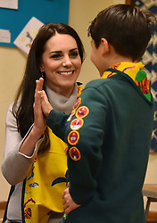 The Duchess of Cambridge, gives a high-five to a cub scout who showed her how to support a broken arm during a Cub Scout Pack meeting with cubs from the Kings Lynn District, in Kings Lynn at the The Scout and Guide Hut in North Wootton, near King's Lynn, for an event to celebrate 00 years of the Cub Scout movement.