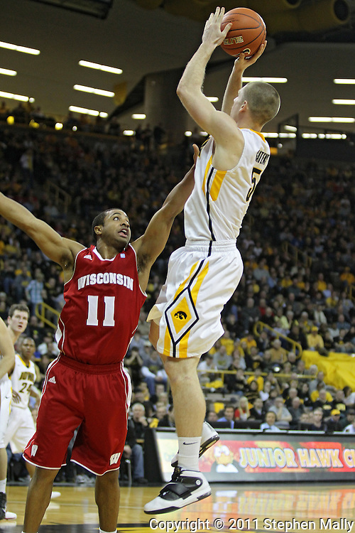 February 09 2011: Iowa Hawkeyes guard Matt Gatens (5) puts up a shot as Wisconsin Badgers guard Jordan Taylor (11) defends during the second half of an NCAA college basketball game at Carver-Hawkeye Arena in Iowa City, Iowa on February 9, 2011. Wisconsin defeated Iowa 62-59.