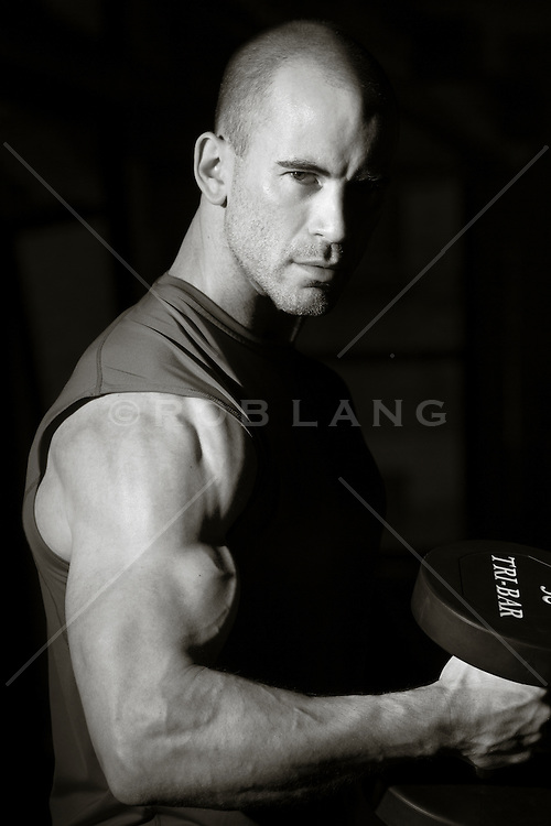bald athletic man lifting weights in a gym