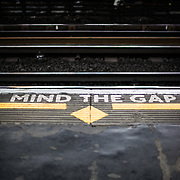 Painted signs on a London Underground platform warning passengers to Mind the Gap between the train and the platform when stepping on and off the train.