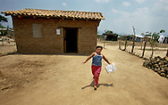 SANTA FE, EL SALVADOR- MAY 2000:  A child runs home from school in the small aldea of Santa Fe, El Salvador. According to UNICEF, only 69% of primary school entrants reach grade 5.  (Photo by Robert Falcetti). .