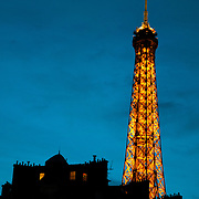 The Eiffel Tower illuminated at night against a deep blue sky of dusk and nearby apartment buildings silhouetted in the bottom of the frame.