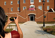 Ohio University student mother Maria Grothause takes a picture of her son and his friends in front of Adams Hall after moving him into his new dorm room Sunday afternoon.