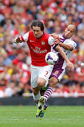 Arsenal's Tomas Rosicky is tackled by Aston Villa's Karim El Ahmadi  - Photo mandatory by-line: Mitch Gunn/JMP - Tel: Mobile: 07966 386802 17/08/2013 - SPORT - FOOTBALL - Emirates Stadium - London -  Arsenal V Aston Villa - Barclays Premier League