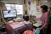 Tsuyako Taira who is 80 years old are watching Japan's prime minister, Shinzo Abe on TV in her temporary housing in Ishinomaki that she is sharing with her son.