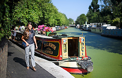 © Licensed to London News Pictures. 24/07/2018. London, UK. A commuter makes her way along the canal towpath at Little Venice in central London, as warm temperatures in the capital continue. Forecasters are predicting record temperatures later this week. Photo credit: Ben Cawthra/LNP