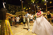 "The Mai Tai bar at the historic Royal Hawaiian Hotel, also known as the ""Pink Lady"". Japanese newlyweds learning Hula."