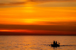 Sport fishers on Lake Michigan enter the Pine River channel near the South Pier Lighthouse during sunset at Charlevoix, Michigan. People fish for Salmon, Steelhead, salmon, brown trout and lake trout in the Lake Michigan waters near Charlevoix.
