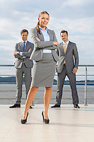 Portrait of confident businesswoman standing with coworkers on terrace against sky