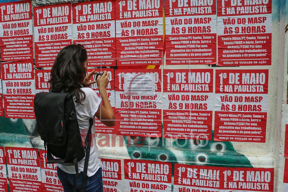 Mulher fotografa recado de foi colado por um homem que se revoltou ao ver diversos cartazes contra a presidenta Dilma colados em um moro que estava grafitado em um palacete na avenida paulista. Sao Paulo 26/04/2016 MARCELO S. CAMARGO/FRAMEPHOTO