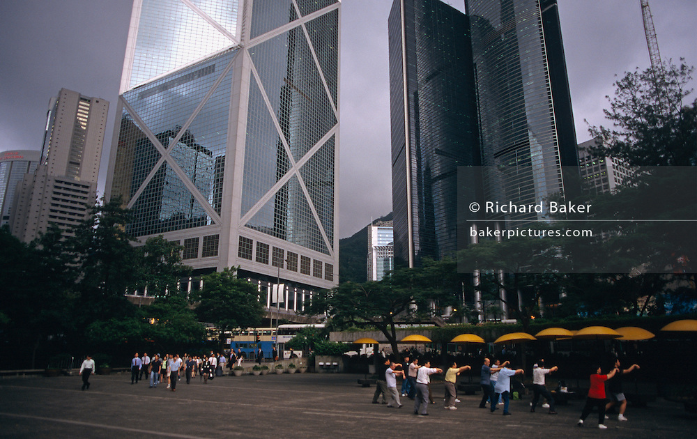 "On the very last day of British rule over its Hong Kong colony, we see two groups representing this colonial territory's population. Commuters walk through Chater Garden about to pass another group of older exercise class. Towering above them all is the Bank of China skyscraper, then the tallest building in Asia, As the last hours tick away before the transfer of sovereignty of Hong Kong from the United Kingdom to the Peoples Republic of China (PRC), often referred to as ""The Handover"" on June 30, 1997. Midnight of that day signified the end of British rule and the transfer of legal and financial authority back to China. Almost 7 million people call a territory of 1100 sq km home, squeezing onto only 10% of the available land space. This is a metropolis of high population density and one of the world's economic powerhouses."