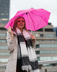 © Licensed to London News Pictures. 01/12/2018. London, UK.  A woman with a pink umbrella walking across London Bridge during rain and wet weather on the first day of meteorological winter.  Photo credit: Vickie Flores/LNP