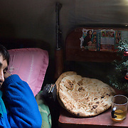 An Afghan National Army soldier lays in his bed beside his assault rifle, bread, tea and a small Christmas tree during the morning on the second day of EID while taking a break from the fighting to celebrate the second EID also known as the Festival of Sacrifice at a Forward Operating Base on the front lines in Zhari District located west of Kandahar City, Afghanistan. Many of the Afghan soldiers serving with Canadian Troops considered EID like their form of Christmas. There are two celebrations of EID during the second it is common to sacrifice an animal, which is to commemorate and celebrate the sacrifice of the Prophet Abraham also known as Ibrahim.<br /> &copy; Louie Palu/ZUMA Press/New America Foundation