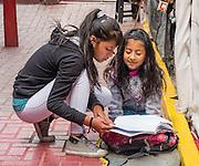 An elder girl tutors one younger, in Huaraz, in the Santa Valley (Callejon de Huaylas), Ancash Region, Peru, Andes Mountains, South America.