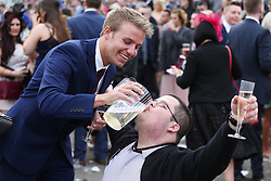 © Licensed to London News Pictures. 08/04/2016. Liverpool, UK. A racegoer celebrates winning by downing drink from a jug on Ladies Day at the Grand National 2016 at Aintree Racecourse near Liverpool. The race, which was first run in 1839, is the most valuable jump race in Europe. Photo credit : Ian Hinchliffe/LNP