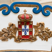 Decoration on the stern of the Custom's Barge, built in Lisbon in the last quarter of the 18th century for the service of the customs inspector. She was manned by 12 oarsmen. The Museu de Marinha (Maritime Museum of Navy Museum) focuses on Portuguese maritime history. It features exhibits on Portugal's Age of Discovery, the Portuguese Navy, commercial and recreational shipping, and, in a large annex, barges and seaplanes. Located in the Belem neighborhood of Lisbon, it occupies, in part, one wing of the Jerónimos Monastery. Its entrance is through a chapel that Henry the Navigator had built as the place where departing voyagers took mass before setting sail. The museum has occupied its present space since 1963.