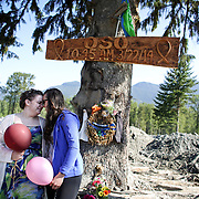 Survivor Amanda Skorjanc, left, and Natasha Huestis embrace at a memorial. Huestis lost her daughter Sanoah Violet Huestis and her mother Christina Jefferds in the Oso Mudslide. Hundreds of Oso, Darrington and Arlington residents walked on State Route 530 and paid tribute to the victims before the highway was reopened to cars. A little more than two months after the Oso mudslide destroyed a neighborhood and killed 43 people, the highway through the heart of the slide reopened to vehicle traffic. Motorists must follow a pilot car that directs a single direction at a time. Photographed on Saturday, May 31, 2014.