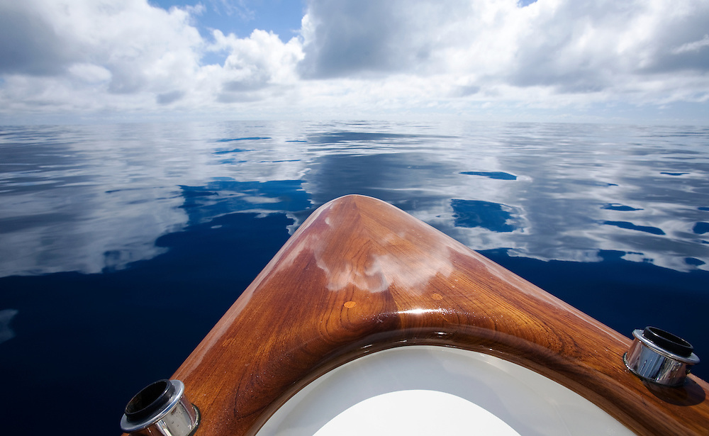 The bow of a sailing yacht motors through a dramatic early morning flat calm sea, very unusual for the North Atlantic Ocean due west of the Azores.