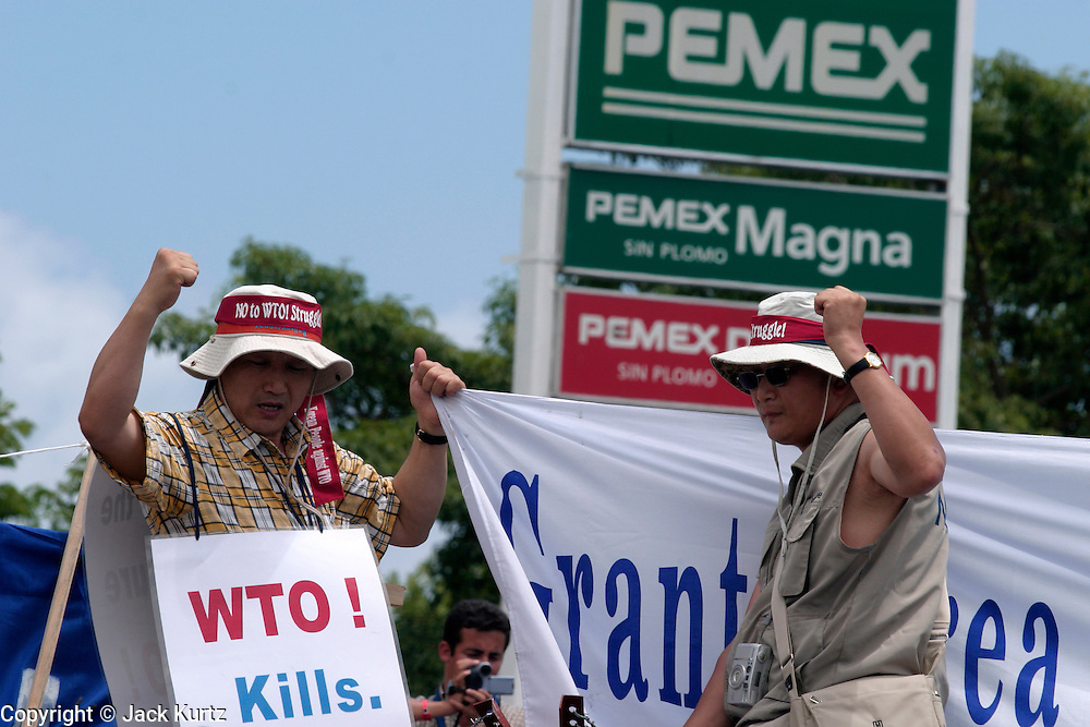 10 SEPTEMBER 2003 - CANCUN, QUINTANA ROO, MEXICO: Lee Kyung-hae, left, and another Korean anti-globalization protestor, string up a banner from atop the fence separating the downtown area from the hotel zone in Cancun, Quintana Roo, Mexico during a protest against the WTO Wednesday. Kyung-hae killed himself during the protest moments later when he stabbed himself in the chest and then fell or jumped from a nearby rooftop. Tens of thousands of people opposed to the WTO have come to this Mexican resort city to protest the 5th Ministerial meeting of the World Trade Organization. The WTO meetings are taking place in the hotel zone of Cancun, about 10 miles from the protestors.  PHOTO BY JACK KURTZ