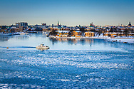 A small ferry on the Stockholm Ström going between Old Town and Djurgården. With City scrapes upper left. Stockholm Sweden, seascapes in winter. Vinter i sjöstaden Stockholm.