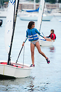 Young girl having fun and fooling around on her dinghy sailboat during summer sailing on Narragansett Bay