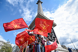 © Licensed to London News Pictures. 01/05/2018. LONDON, UK.  Demonstrators wave flags around Nelson's Column during the annual May Day Rally on International Workers' Day.  People marched through central London to a rally in Trafalgar Square.  Photo credit: Stephen Chung/LNP