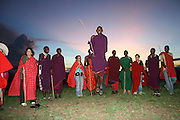 Africa, Tanzania, Maasai dancing with European tourists in traditional robes at sunset an ethnic group of semi-nomadic people April 2006