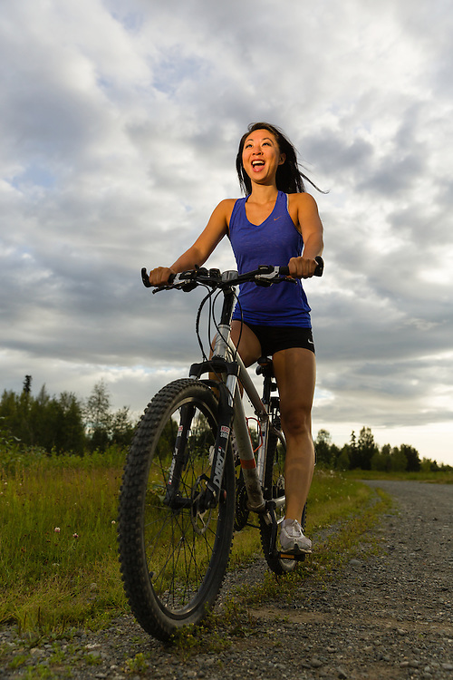 Woman riding bike on Joint Base Elmendorf Richardson at Six Mile Lake near Anchorage in Southcentral Alaska. Summer. Evening.