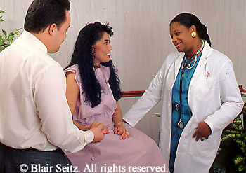 Doctor, Physician at Work, African-American Physician Examines Hispanic Patient and Hispanic Husband Attends