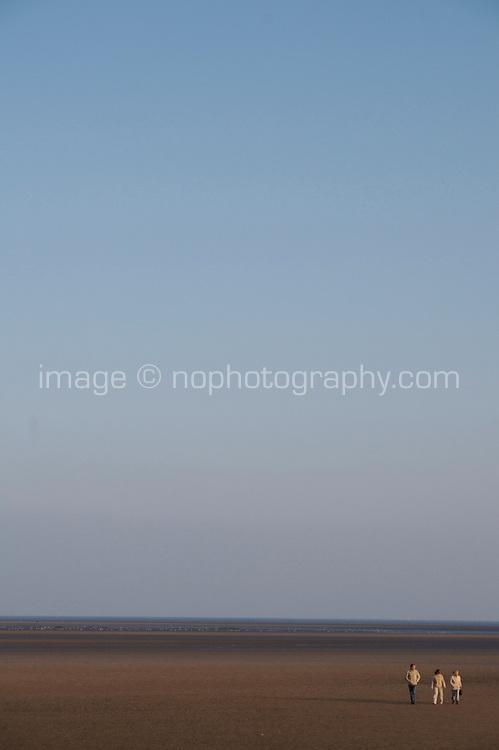 Three people walking on Sandymount Strand in Dublin Ireland on a winters evening