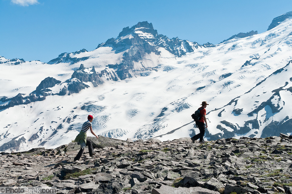 Two hikers, Emmons Glacier, and Little Tahoma seen on Burroughs Mountain Trail, Mount Rainier National Park, Washington, USA. For vigorous training, hike Burroughs Mountain 10 mile loop, 3200 feet ascent, from White River Campground up Glacier Basin Trail, back via Shadow Lake, Mount Rainier National Park, Washington