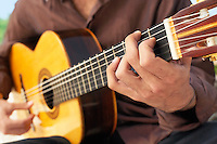 Man Playing classical guitar mid section close-up.