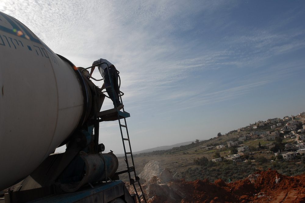 An Israeli cement truck driver is working in a new neighborhood in Beit Arye settlement.