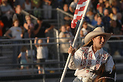 2005 Miss Rodeo Michigan Katie Ervay of Shelby, Michigan rides with the American flag during the opening of the Excalibur Rodeo at the 2009 Emmet/Charlevoix County Fair.