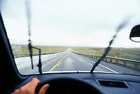 Drivers view while driving on a wet highway through a high desrt landscape in Central Utah, USA.