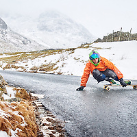 A photograph of a downhill skateboarder on the struggle, near kirkstone pass, during the beast from the east in the Lake District, Cumbria