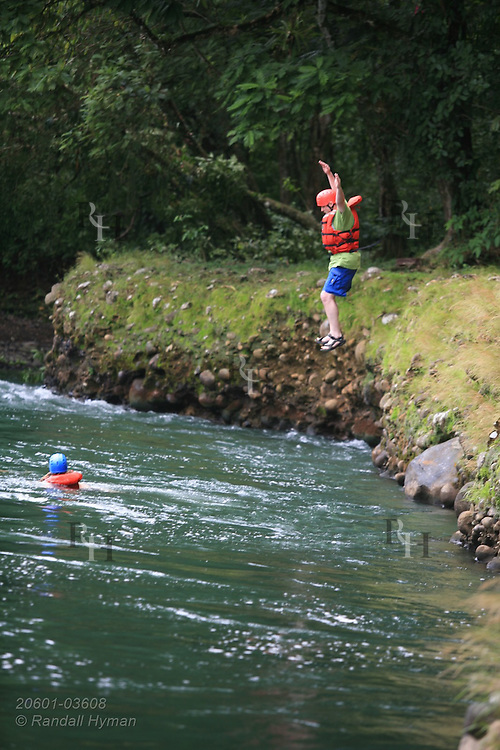 Man jumps into Sarapiqui River at start of whitewater raft trip; Las Horquetas, Costa Rica.