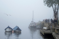© Licensed to London News Pictures. 01/11/2015. Kingston, UK. People walk through he fog along the towpaths.  Fog along the River Thames in Kingston today, 1st November 2015. Much of the South East of Britain woke to fog this morning. Photo credit : Stephen Simpson/LNP
