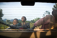 Children hang on the back of the vehicle, as international buyers come to tour Buf Coffee's Nyarusiza Coffee Washing Station in southern Rwanda.