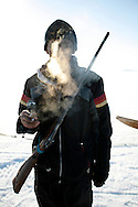 Manik, 16, smokes while taking a break from seal hunting in Resolute Bay, Canada on Tuesday, June 12, 2007. Inuit hunters like Manik hunt seals for food, and their community uses every part of the seals, either eating the meat or using the hides to make warm clothes. The traditional way of life in the Resolute Bay Inuit community is being threatened by rising temperatures. The dangers of global warming, which have been extensively documented by scientists, are appearing first, with rapid, drastic effects, in the Arctic regions where Inuit people make their home. Inuit communities, such as those living on Resolute Bay, have witnessed a wide variety of changes in their environment. The ice is melting sooner, depleting the seal population and leaving them unable to hunt the animals for as long. Other changes include seeing species of birds and insects (such as cockroaches and mosquitoes) which they have never encountered before. The Inuit actually lack words in their local languages to describe the creatures they have begun to see. ....