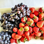 Fresh purple grapes and red strawberries on a white plate.<br /> <br /> For all details about sizes, paper and pricing starting at $85, click &quot;Add to Cart&quot; below.