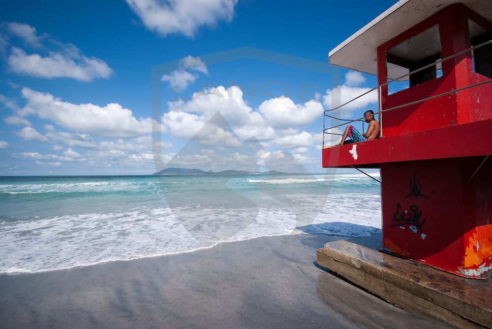 lifeguard stand with carioca sitting and watching the ocean tide and beautiful landscape with cloud filled blue sky at cabo frio beach, rio de janeiro, brazil.