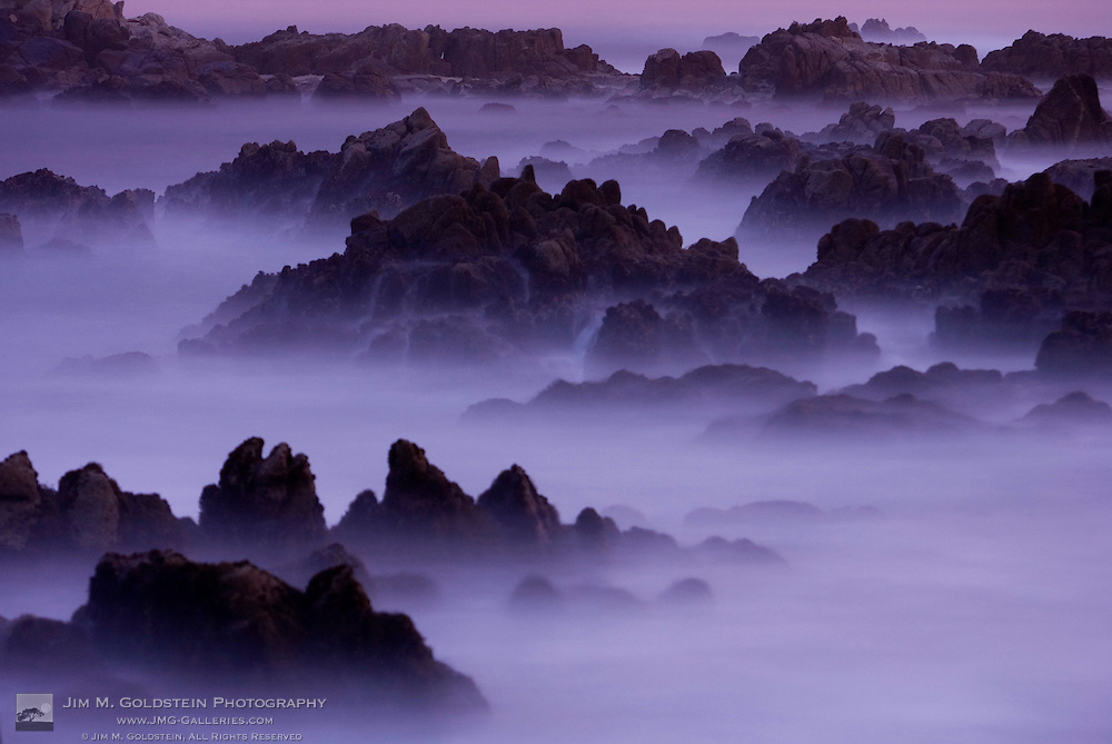 Surf pours over the California coastline at dusk at Asilomar State Beach.