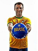 one man with Brazilian jersey giving soccer ball isolated in white background