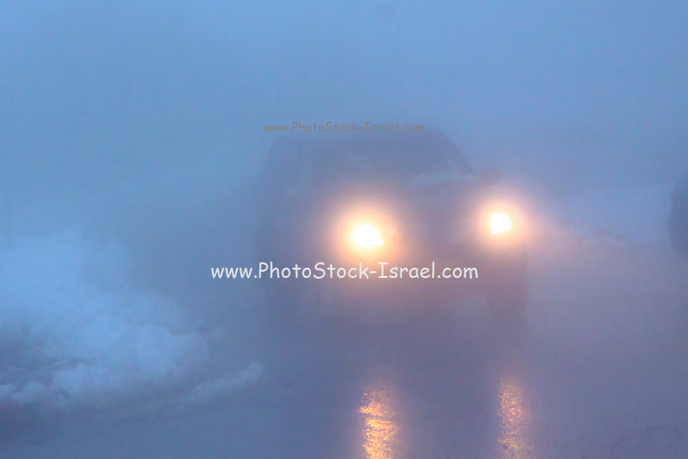 Single car travels on a foggy mountain road