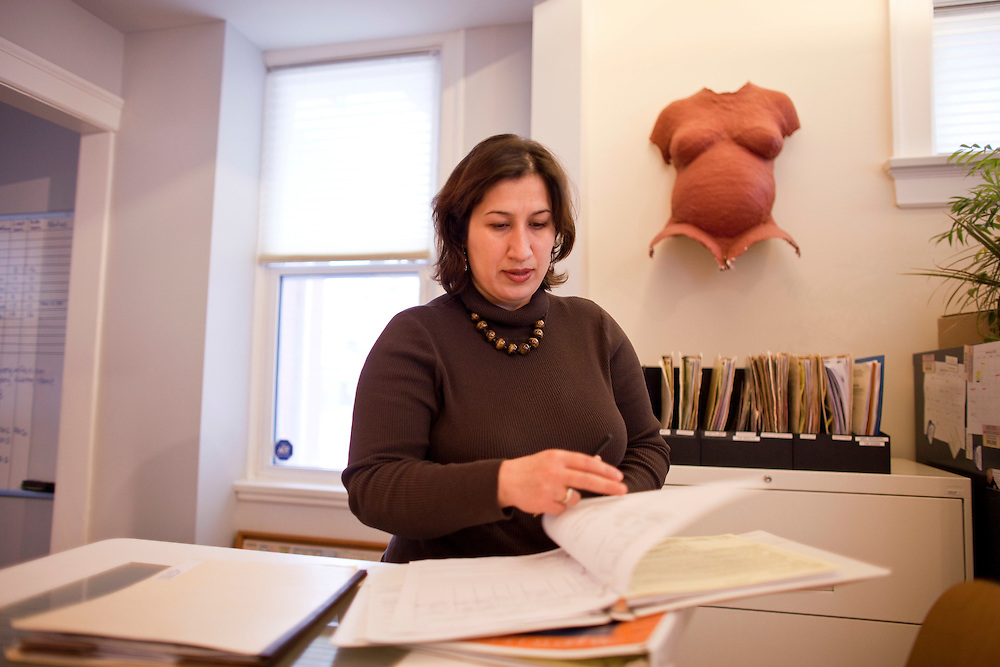 London, Ontario ---10-02-16--- Mojgan Nadafi, looks over some paperwork at Thames Valley Midwives where she works in London, Ontario, February 16, 2010. In Iran, Mojgan was a well regarded academic in midwifery with her masters degree yet when she immigrated to Canada she had difficulty getting her qualifications recognized.<br /> GEOFF ROBINS The Globe and Mail