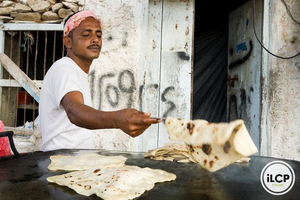 Yemeni man making local bread on skillet, Hawf Protected Area, Yemen
