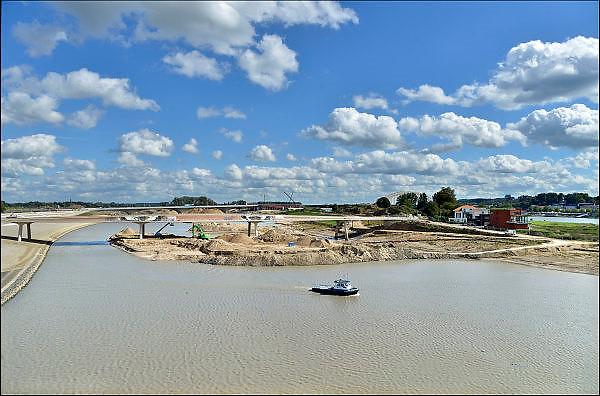 Nederland, Nijmegen, 15-9-2015De nevengeul aan de overkant van de Waal bij Lent nadert zijn voltooiing. Laatste werkzaamheden. Grootste onderdeel van de vele werken van Rijkswaterstaat om bij hoogwater een betere waterafvoer in de rivier te hebben. Het is een omvangrijk project waarbij onder meer de pijlers van het spoorviaduct een bredere basis kregen omdat die straks in de loop van het water staan. Ook de n325 die vanaf de Waalbrug naar Arnhem loopt is over 400 meter opnieuw aangelegd omdat het talud vervangen wordt door een nieuwe brug met drie gracieuze pijlers. Het dorp veurlent komt op een kunstmatig eiland te liggen met twee bruggen als ontsluiting. Een voetgangersbrug en een andere, de Promenadebrug, voor normaal verkeer. Inmiddels begint de nieuwe kade aan de noordkant van deze geul vorm te krijgen. Ruimte voor de rivier, water, waal. In de nieuwe dijk wordt een drempel gebouwd die stapsgewijs water doorlaat en bij hoogwater overloopt.The Netherlands, NijmegenMeasures taken by Nijmegen to give the river Waal, Rhine, more space to flow during highwater and to prevent the risk of flooding. Room for the river. Reducing the level, waterlevel. Large project to create a new paralel gully, an extra flow of water, so the river can drain more water during highwater. Due to climate change and expected rise, increase of the sealevel, the Dutch continue to protect their land from the water.Foto: Flip Franssen/HH