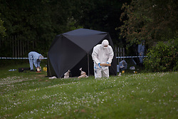 © licensed to London News Pictures. 29/05/2012. London, UK. Forensic officers investigating the crime scene where the body of an 18-year-old was found on Chigwell Road, close to Broadmead Fields in Woodford Green. Photo credit: Tolga Akmen/LNP